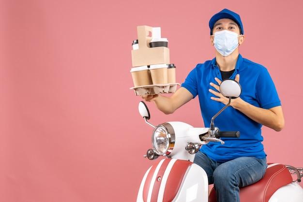 Bovenaanzicht van een dankbare mannelijke bezorger met een masker die een hoed draagt die op een scooter zit en bestellingen aflevert op perzik