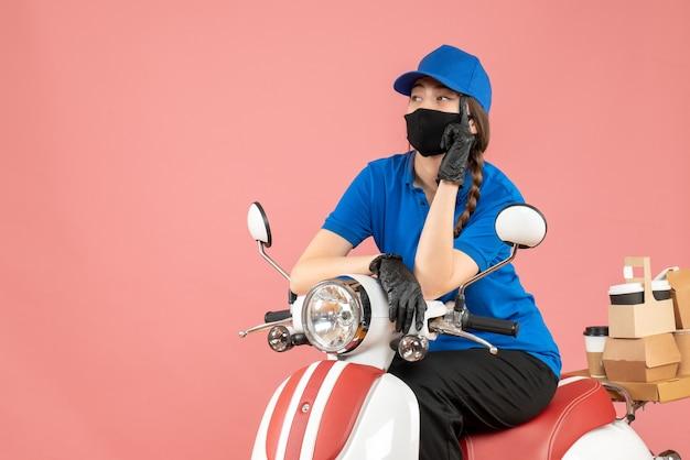 Bovenaanzicht van een denkend koeriersmeisje met een medisch masker en handschoenen die op een scooter zitten en bestellingen afleveren op pastel perzik