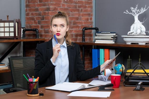 Bovenaanzicht van een denkende jonge vrouw die aan een tafel zit en een document op kantoor vasthoudt