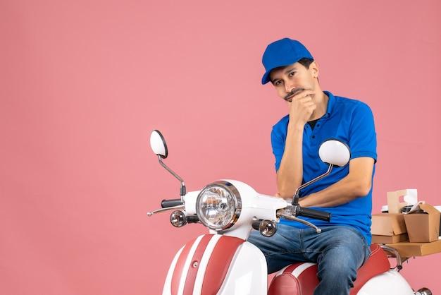 Bovenaanzicht van een denkende koeriersman met een hoed die op een scooter zit en bestellingen aflevert op pastel perzik