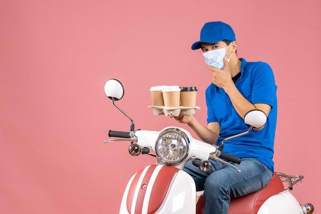 Bovenaanzicht van een denkende koeriersman met een masker met een hoed die op een scooter zit en bestellingen op pastel perzik toont