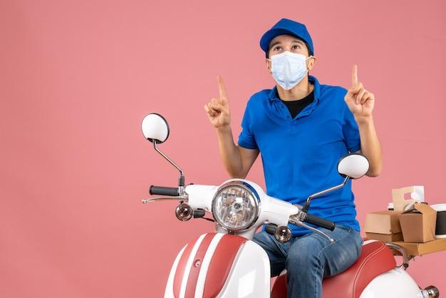Bovenaanzicht van een denkende koeriersman met een medisch masker met een hoed die op een scooter zit en bestellingen aflevert en naar boven wijst op pastel perzik