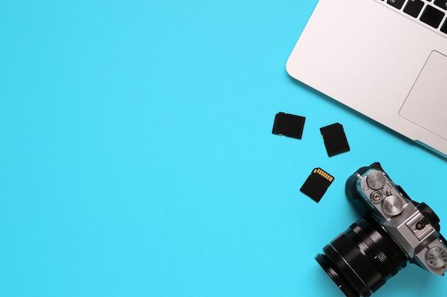 Bovenaanzicht van een desktop van een fotograaf bestaande uit een camera, een laptop, een notebook en een geheugenkaart op een blauwe achtergrond van het bureau - kopieer de ruimte.