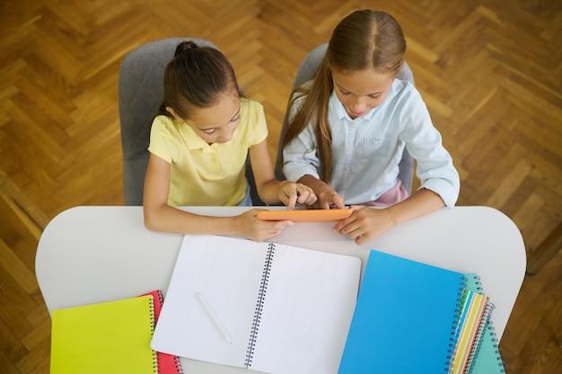 Bovenaanzicht van een donkerharig meisje en haar blonde klasgenoot zittend met een gadget aan het bureau