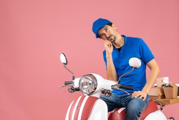 Bovenaanzicht van een doordachte koeriersman met een hoed die op een scooter zit en bestellingen aflevert op pastel perzik