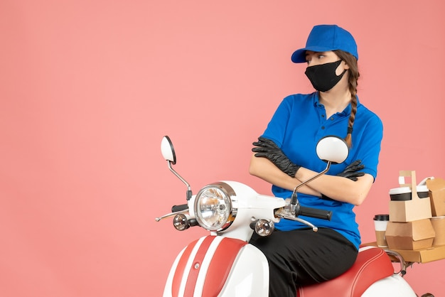 Bovenaanzicht van een doordachte koeriersvrouw met een medisch masker en handschoenen die op een scooter zit en bestellingen aflevert op pastel perzik