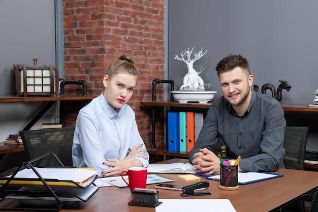 Bovenaanzicht van een druk kantoorteam dat aan tafel zit en een belangrijk onderwerp op kantoor bespreekt