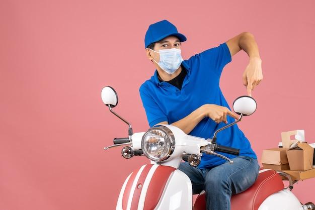 Bovenaanzicht van een drukke bezorger met een medisch masker met een hoed die op een scooter zit en naar beneden wijst op een pastelkleurige perzikachtergrond