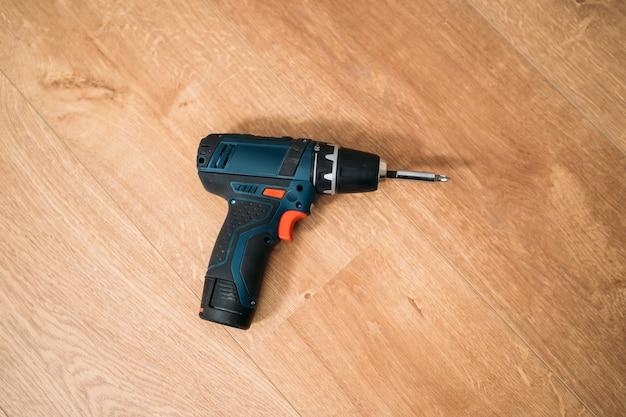 Bovenaanzicht van een elektrische schroevendraaier op houten vloer