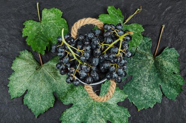 Bovenaanzicht van een emmer met zwarte druiven met bladeren op zwarte ondergrond