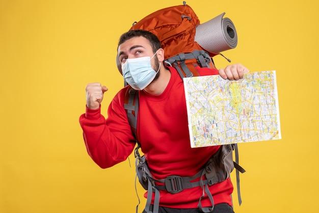 Bovenaanzicht van een emotioneel denkende reiziger die een medisch masker draagt met een rugzak met een kaart op een gele achtergrond