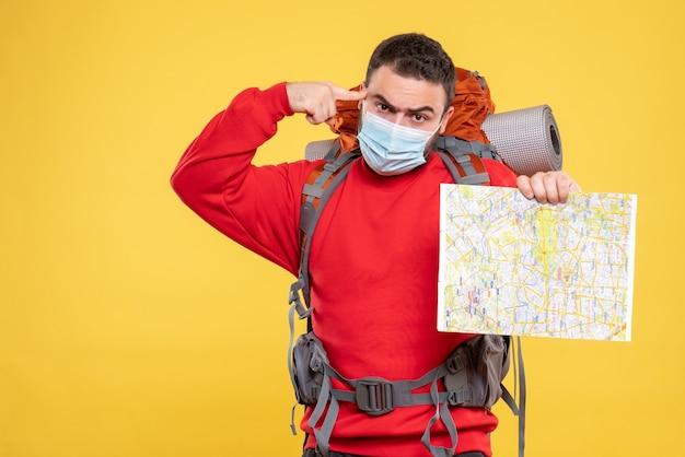 Bovenaanzicht van een emotionele, attente reiziger die een medisch masker draagt met een rugzak met een kaart op een gele achtergrond