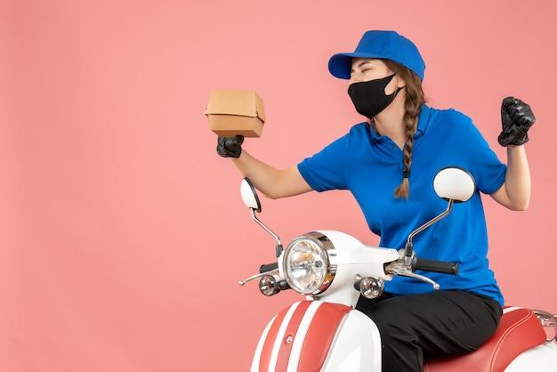 Bovenaanzicht van een emotionele bezorger met een medisch masker en handschoenen die op een scooter zit en bestellingen aflevert op een pastelkleurige perzikachtergrond