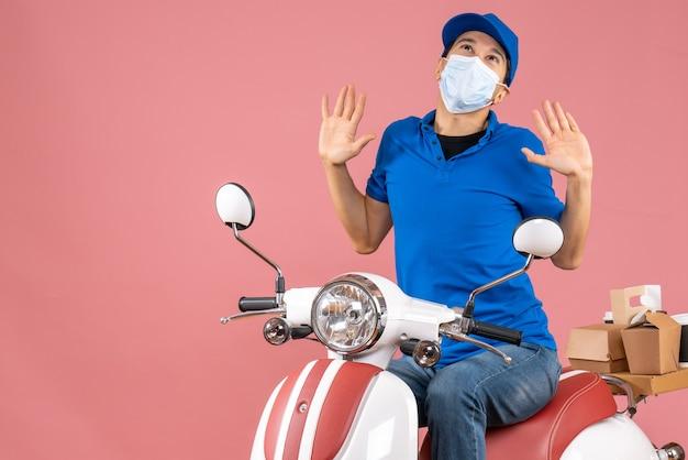 Bovenaanzicht van een emotionele bezorger met een medisch masker met een hoed die op een scooter zit en omhoog kijkt op een pastelkleurige perzikachtergrond