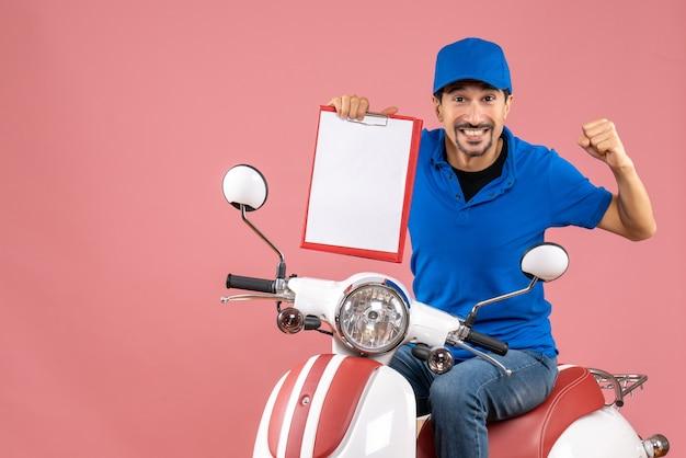Bovenaanzicht van een emotionele koeriersman met een hoed die op een scooter zit en een document toont op een pastelkleurige perzikachtergrond