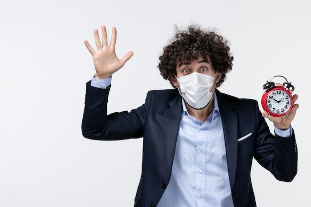 Bovenaanzicht van een emotionele zakenman in pak en met zijn masker met een klok met vijf