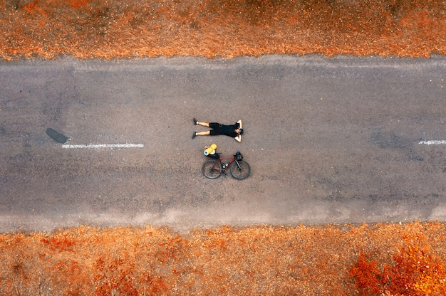 Bovenaanzicht van een fietser met een racefiets liggend op het asfalt.