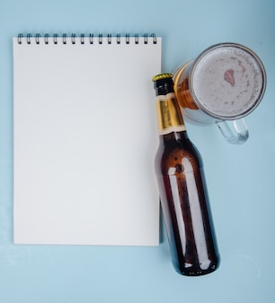 Bovenaanzicht van een flesje bier met een schetsboek en glas bier op blauw