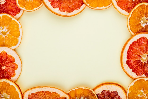 Bovenaanzicht van een frame gemaakt van gedroogde plakjes sinaasappel en grapefruit gerangschikt op witte achtergrond met kopie ruimte