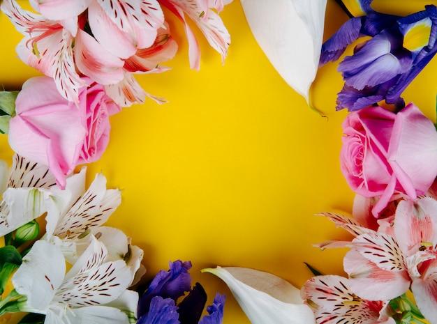 Bovenaanzicht van een frame gemaakt van mooie bloemen roze rozen alstroemeria donkerpaarse iris en witte calla lelies kleuren op gele achtergrond met kopie ruimte