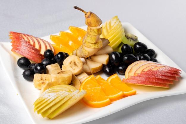 Bovenaanzicht van een fruitsalade met aardbeien, sinaasappelen, kiwi, bosbessen en perziken. fruit snijwerk concept