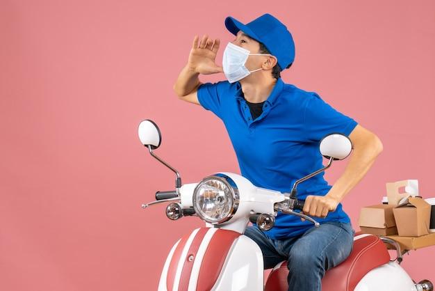 Bovenaanzicht van een geconcentreerde bezorger met een medisch masker met een hoed op een scooter op een pastelkleurige perzikachtergrond
