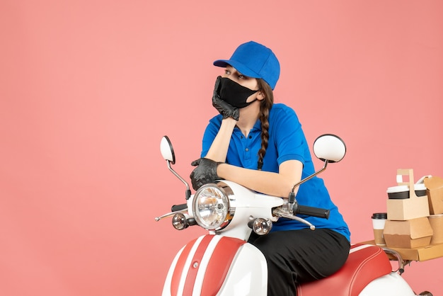 Bovenaanzicht van een gefocuste koeriersvrouw met een medisch masker en handschoenen die op een scooter zit en bestellingen aflevert op een pastelkleurige perzikachtergrond