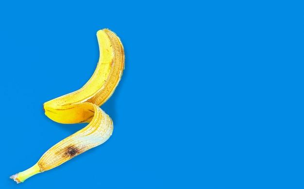 Bovenaanzicht van een gele bananenschil op een blauw oppervlak