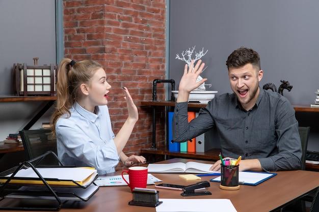 Bovenaanzicht van een gelukkig en glimlachend managementteam dat aan tafel zat, kwam tot onderhandeling in de vergaderruimte op kantoor