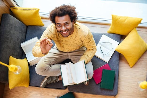 Bovenaanzicht van een gelukkige afro-amerikaanse jongeman die een boek leest en thuis een ok teken toont