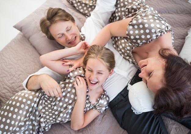 Bovenaanzicht van een gelukkige jonge positieve familie charmante vader moeder en dochter tiener lachen en gek rond op de bank. concept van een liefdevolle familie