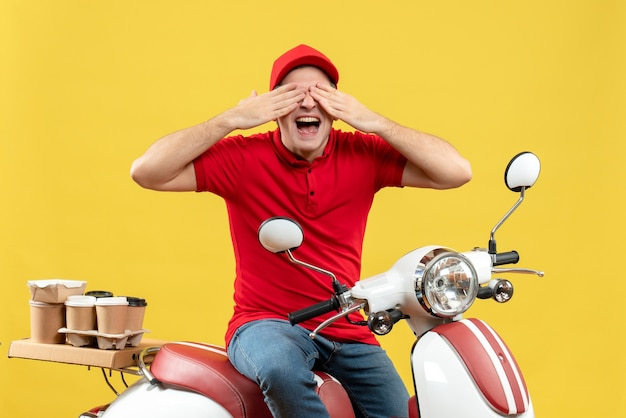 Bovenaanzicht van een gelukkige jonge volwassene die een rode blouse en een hoed draagt die bestelling levert, zittend op een scooter en sluit zijn ogen op gele achtergrond