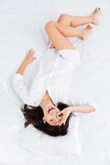 Bovenaanzicht van een gelukkige jonge vrouw die in bed ligt en een goed gebaar toont
