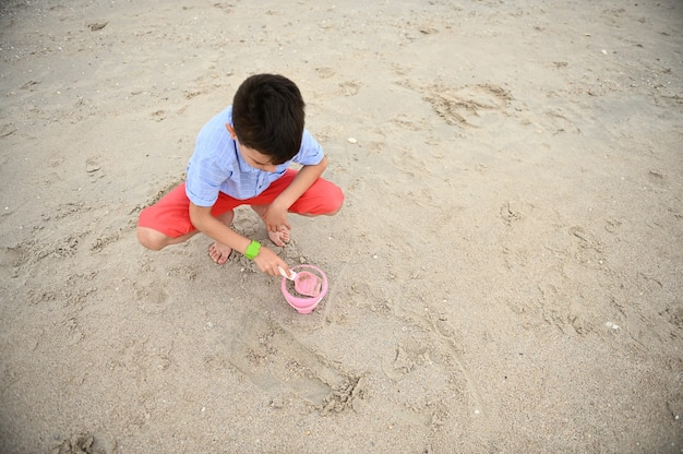 Bovenaanzicht van een gelukkige, knappe en schattige peuter die speelgoedemmer vult met zand om te bouwen