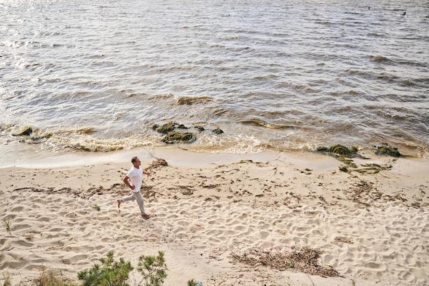 Bovenaanzicht van een gelukkige sportieve man die de ochtend begint met cardiotraining en joggen op het strand
