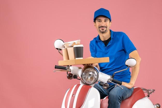 Bovenaanzicht van een gelukkige, tevreden koeriersman met een hoed die op een scooter zit op een pastelkleurige perzikachtergrond
