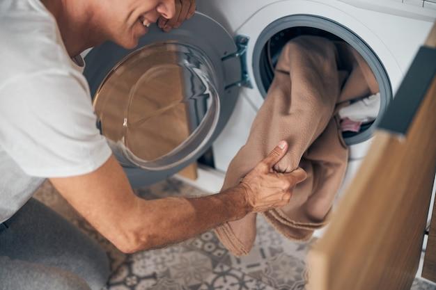 Bovenaanzicht van een gelukkige volwassen man die thuis routine doet en thuis bij de wasmachine staat