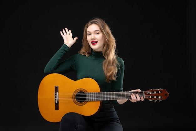 Bovenaanzicht van een gelukkige vrouwelijke muzikant die gitaar vasthoudt en er vijf op het donker laat zien
