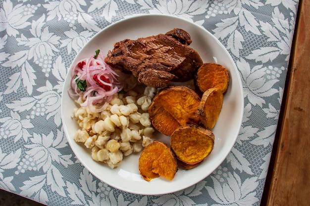 Bovenaanzicht van een gerecht met rundvlees, zoete aardappelen en maïs