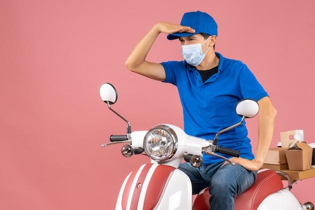 Bovenaanzicht van een gerichte bezorger met een medisch masker met een hoed op een scooter op een pastelkleurige perzikachtergrond