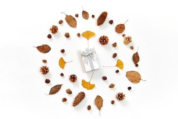 Bovenaanzicht van een geschenk in het midden van een krans gemaakt van herfstbladeren en coniferenkegels op wit
