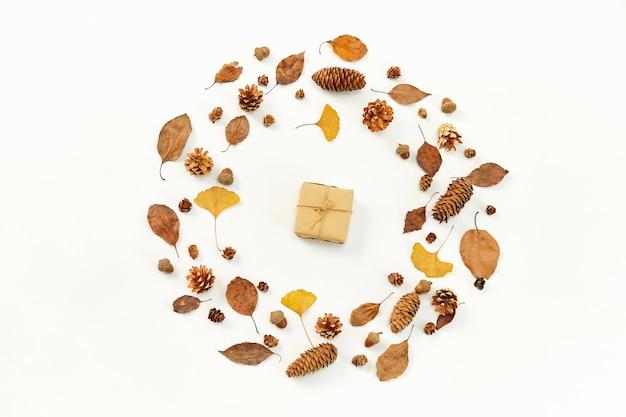 Bovenaanzicht van een geschenk in het midden van een krans gemaakt van herfstbladeren en coniferenkegels op witte backgr