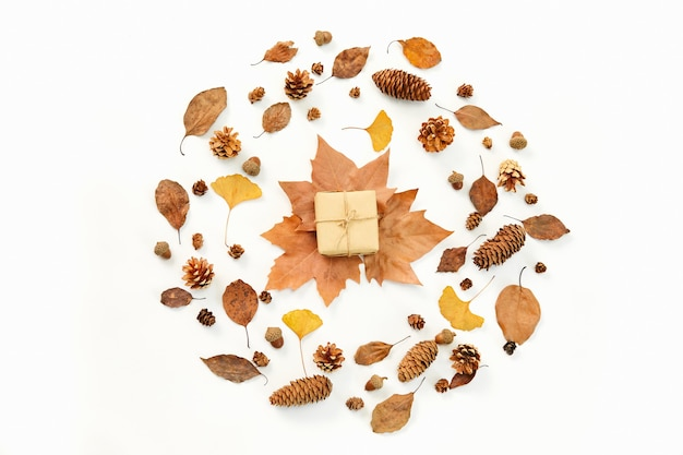 Bovenaanzicht van een geschenk in het midden van een krans gemaakt van herfstbladeren en coniferenkegels
