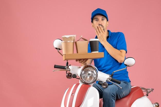 Bovenaanzicht van een geschokte, emotionele koeriersman met een hoed op een scooter op een pastelkleurige perzikachtergrond peach