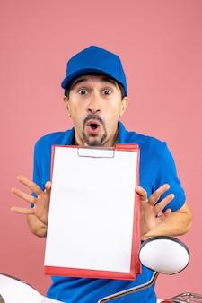 Bovenaanzicht van een geschokte mannelijke bezorger met een hoed die op een scooter zit en document toont