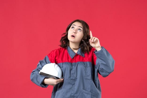 Bovenaanzicht van een geschokte vrouwelijke bouwer in uniform en met een helm die omhoog wijst op een geïsoleerde rode achtergrond