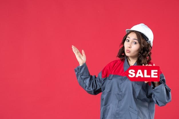 Bovenaanzicht van een geschokte vrouwelijke bouwer in uniform met een helm en een verkooppictogram dat aan de rechterkant op geïsoleerde rode achtergrond omhoog wijst
