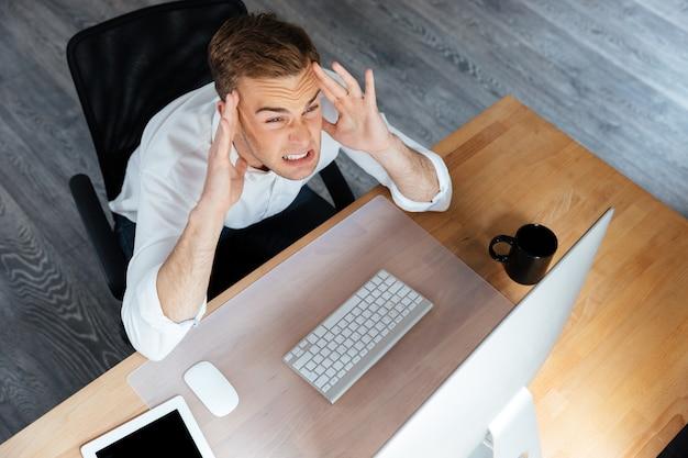Bovenaanzicht van een gestresste jonge zakenman die met de computer werkt en hoofdpijn heeft op kantoor