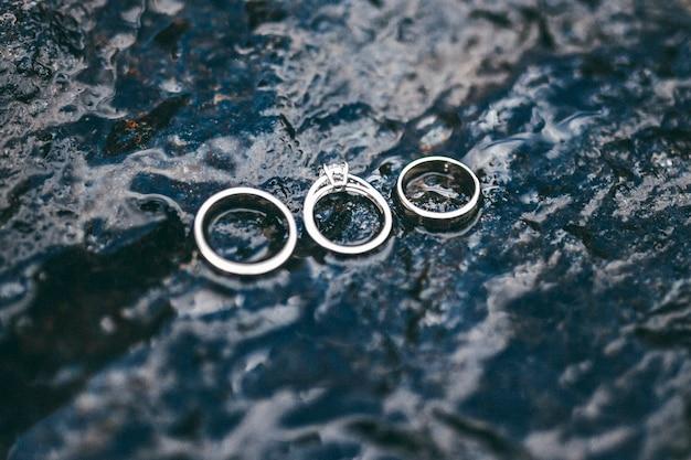 Bovenaanzicht van een geweldige ringen van een bruid en bruidegom op een geweldige natte berg blauwe rivier in de bergen.