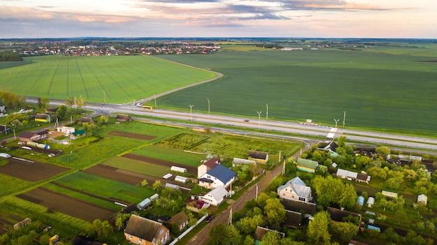 Bovenaanzicht van een gezaaid groen veld en een klein dorpje in wit-rusland. agrarische velden in het dorp.